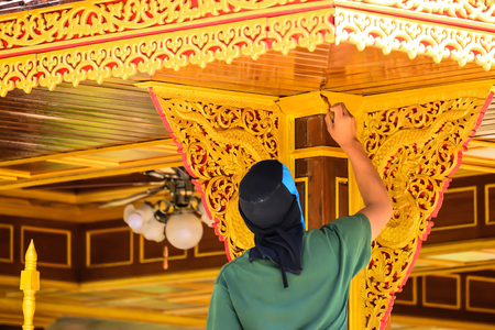The painter uses a brush to paint the wood with a golden yellow color to make the thing more distinctive. Stok Fotoğraf