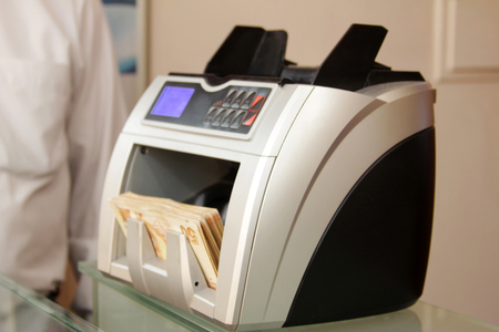 over the counter: Money counting machine Stock Photo