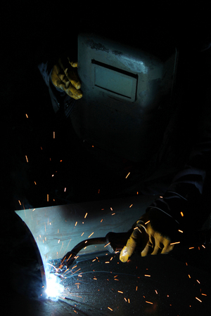 professional welding worker and sparks Stock Photo
