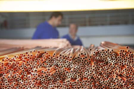 Copper pipes in factory, industrial background. Metal workers in factory. 免版税图像