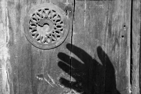 shadow of hand over old wooden door