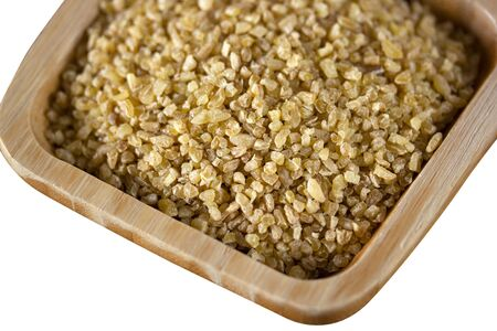 raw wheat grains in wooden plate