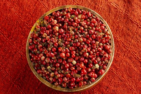 red peppercorn seeds in wooden plate