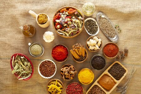 Various spices and herbs as a background.