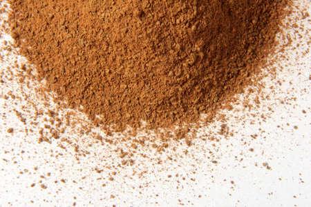 Cinnamon powder heap isolated on white background