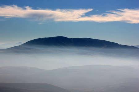 Foggy mountain landscape and blue sky.