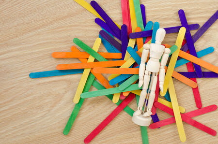 Puppet and colored wood sticks on top wooden table photo