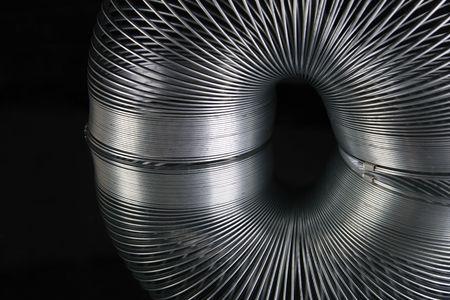 Metal Slinky spring reflected on black