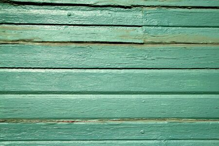 Painted green wooden boards on the side of a house photo