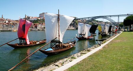 Boats carrying wine docked after arrival, with sails furled, on the banks of the Douro River in Porto, Portugal.