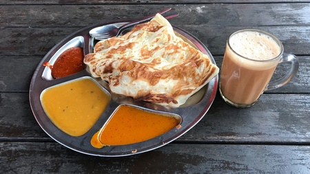 Roti Canai with dhal curry and Teh Tarik om rusty wood table isolated. Indian and asian food