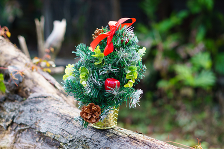 Miniature of Christmas tree with decoration isolated on textured tree in nature background. Selective focus. Holiday concept. Stock Photo