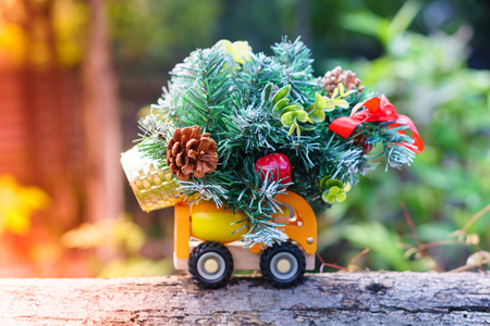 Miniature of lorry toy with Christmas tree isolated on wood, with blurred nature background. Selective focus. Holiday concept.