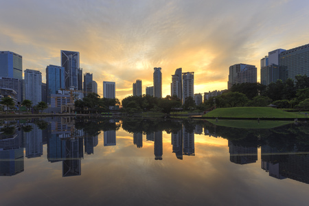 Dramatic and beautiful sunrise scenery with reflection of the symphony lake Kuala Lumpur city. Landscape, architecture and cityscape