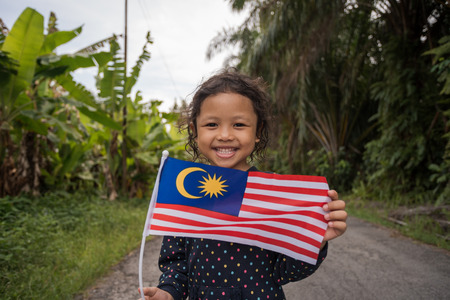 Portrait of young joyful girl with Malaysia flag. Merdeka theme concept. Malaysia's Independence Day. Selective focus. 스톡 콘텐츠