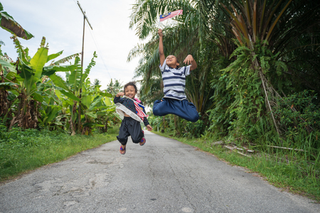 Portrait of playful and joyful two siblings of children with Malaysia flag in nature background, patriotic theme concept. Selective focus. Copy space.