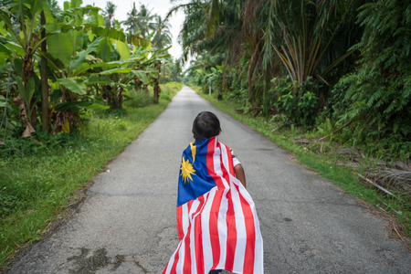 Joyful young boy with Malaysia flag in nature background. Merdeka theme, Malaysia's Independence Day. Selective focus.