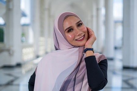 Attractive young stylish woman wearing shawl or hijab, smile and posing. Stock Photo