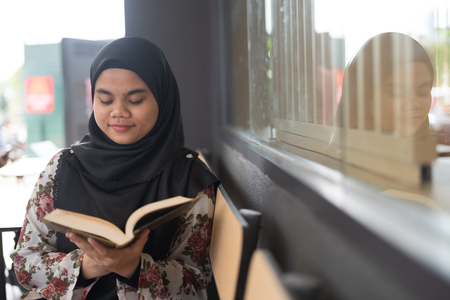 Young cute Muslim Asian woman sitting and reading a book, while chilling and relaxing at restaurant. Student life, study for education concept.