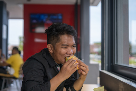 A young man eating burger with funny face at restaurant.