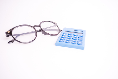 Mini calculator and spectacle glass on white background for copy space. Any pupose conceptual image 写真素材