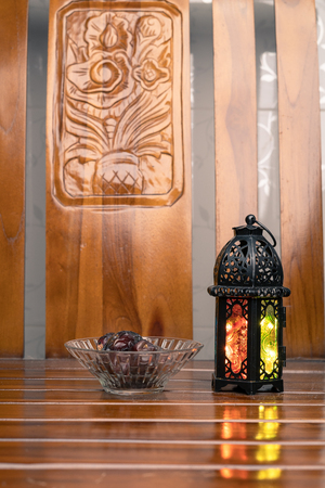 Islamic decorative or ornaments, lantern and dates, kurma isolated on shine wooden background, iftar preparation, fasting in Ramadan concept. Selective focus.