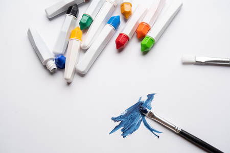 Brushes and bottles of water colors on white background, frame, copy space top view, close up selective focus. Back to school, educations, artistic conceptual.