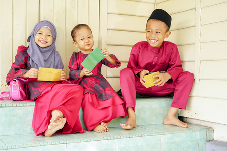 Three kids, happy siblings received money pocket or known as duit raya during Hari Raya Puasa or Eid Mubarak celebration. Muslim in Malaysian celebrate Eid with visiting other family and gathering