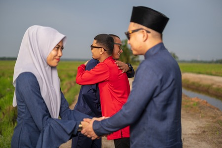 muslim friends and families visiting home and greet embrace each other celebrating eid mubarak handshaking ask for forgiveness as Asian Muslim culture during with paddy background. Selective focus.
