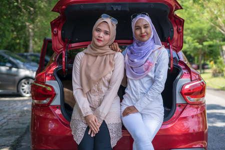 Two Malay young women sitting on car boot