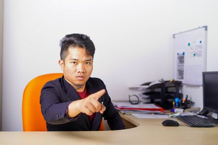 Arguing, conflict, business concept. The conflict between boss and employees. Young Asian man as boss or manager give a command with angry, mad face expression in office. Imagens
