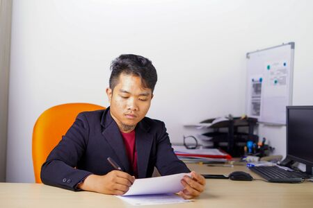 Young Asian man in office writing and reading a paperwork, or sign a contract in casual outfit