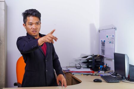 Arguing, conflict, business concept. The conflict between boss and employees. Young Asian man as boss or manager give a command with angry, mad face expression in office. Stock Photo