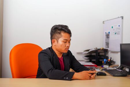 Young Asian man sitting in office doing work on phone or desktop computer in casual outfit.