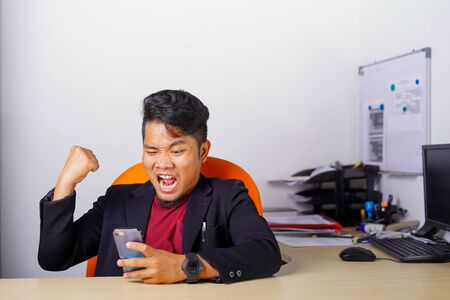 Young Asian man with excited, happiness, surprised face expression sitting or standing up in office, casual suit outfit, successful man achieve the goal. Stock Photo
