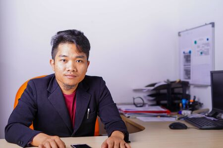 young asian man in casual outfit in office smiling, looking at camera.