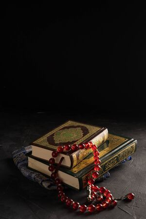 Faith in Islam, Holy book Islamic scripture al-Quran and rosary beads on dark background. Islamic holiday celebration Eid Mubarak or Ramadan Kareem concept. Imagens
