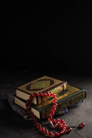 Geloof in de islam, heilige boek islamitische schrift al-Quran en rozenkrans kralen op donkere achtergrond. Islamitische feestdag Eid Mubarak of Ramadan Kareem concept.