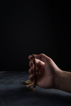 Faith in Islam, rosary beads on dark background. Islamic holiday celebration Eid Mubarak or Ramadan Kareem concept. Copy space. Imagens