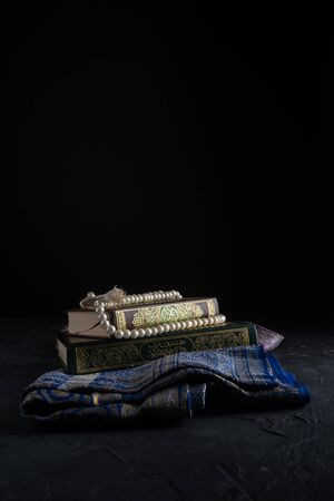 Foi en l'Islam, livre sacré Écriture islamique al-Coran et chapelet sur fond sombre. Célébration de la fête islamique Eid Mubarak ou Ramadan Kareem concept. Banque d'images