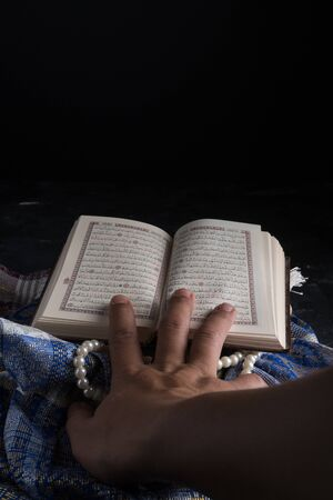Kuala Lumpur, Malaysia - January 19th, 2020 : Faith in Islam, Holy book Islamic scripture al-Quran and rosary beads on dark background. Islamic holiday celebration Eid Mubarak or Ramadan Kareem concept. copy space
