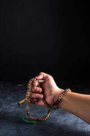Faith in Islam,hand holding rosary beads on dark background. Islamic holiday celebration Eid Mubarak or Ramadan Kareem concept. Copy space. Imagens