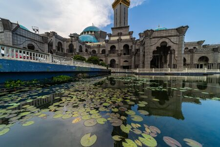 Beautiful wide view of Masjid Wilayah Persekutuan or known as Federal Territory Mosque in Kuala Lumpur, with reclection by the lake at daylight.