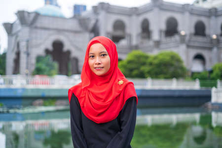 Young attractive Muslim woman in red hijab posing at Federal Territory Mosque of Kuala Lumpur Imagens