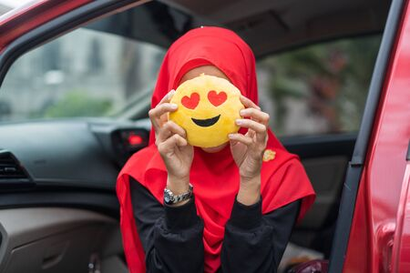 Young woman cover her face with love emoji pillow, happy woman with face expression.