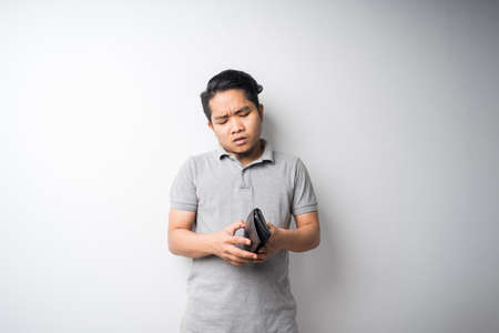 Young Asian man, stressful face expression when looking in empty wallet, economy problem, bankruptcy or broke concept, isolated portrait, selective focus