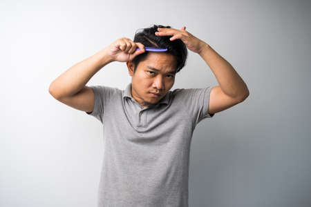 young Asian man comb his hair isolated selective focus