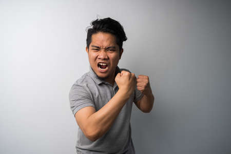 portrait of young man with excited face showing off his fist and punch, motivated, success concept. Isolated selective focus.
