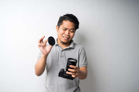 Young Asian man face expression with dslr or mirrorless camera. Photography, creative industry. Isolated selective focus. Stock Photo