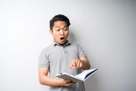 Portrait of Asian man holding book with face expression Stock Photo